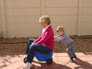 Child_pushing_grandmother_on_plastic_tricycle