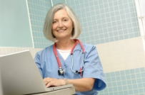 senior female doctor wears blue scrubs with a red stethoscope around her neck while seated at a table and laptop smiling