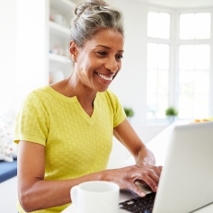 African American Woman Using Laptop In Kitchen At Home